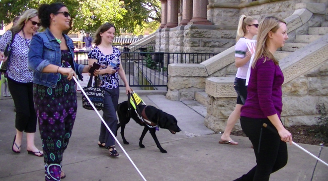 I am walking with my guide dog along with several other sighted peers and supporters who are using a white cane as we walk around the Square.