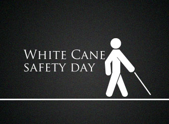 """White Cane Safety Day"" is written in white text on a black background with a white symbol of a person walking with a cane."