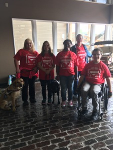 Several people in red shirts posing - one lady with a yellow lab, one lady with a black lab, two other ladies standing, one male standing, and one male in a wheelchair