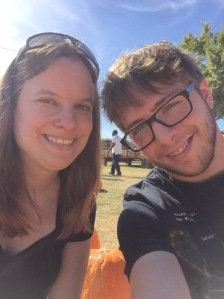 Jessica and Steven (white female and male) doing a selfie with pumpkins in the background.