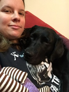 Selfie style pic of Makiko (black Labrador) laying on Jessica (Caucasian woman) who is wearing a black tshirt with white writing. Makiko is cuddled against Jessica's chest resting, with her eyes closing as she rests. One of her purple toys is sitting on the couch beneath her.